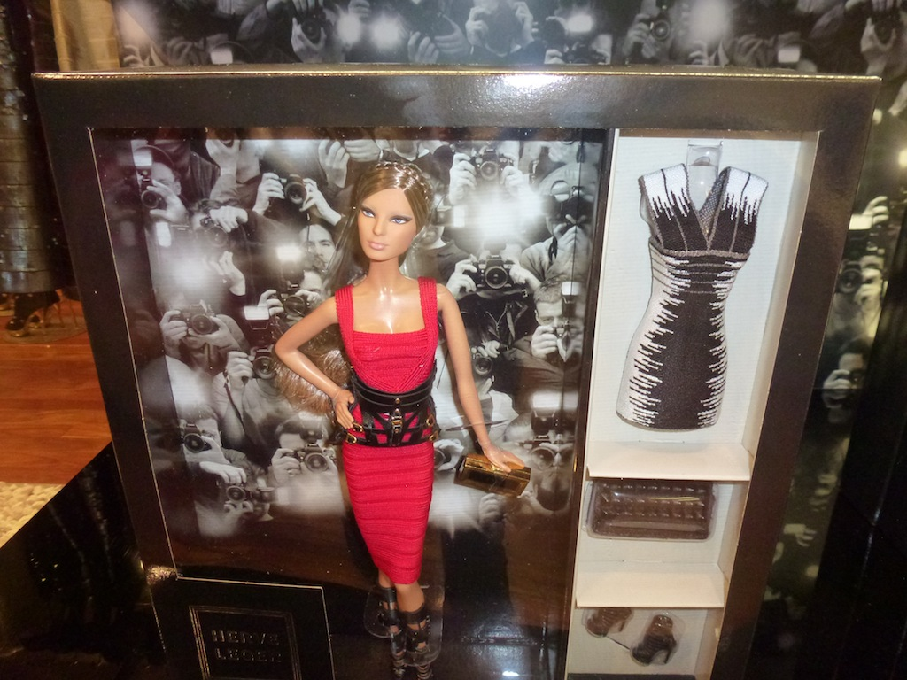 Herve Leger By Max Azria Barbie Doll wears a red bandage dress with harness belt. Glam doll fashion