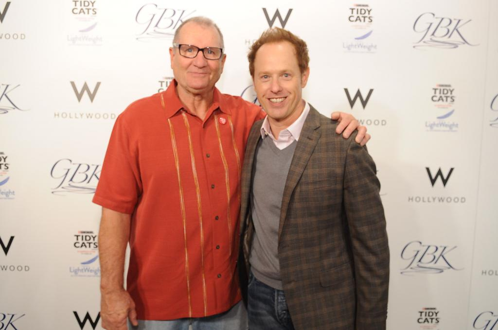 Ed O Neill and Raphael Sbarge posing on the red carpet at GBK celebrity gifting lounge in honor of Emmy Awards.