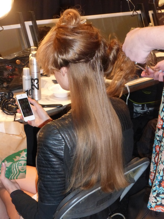 Backstage at NYFW Zimmermann show model gets hair ready for the show NYFW